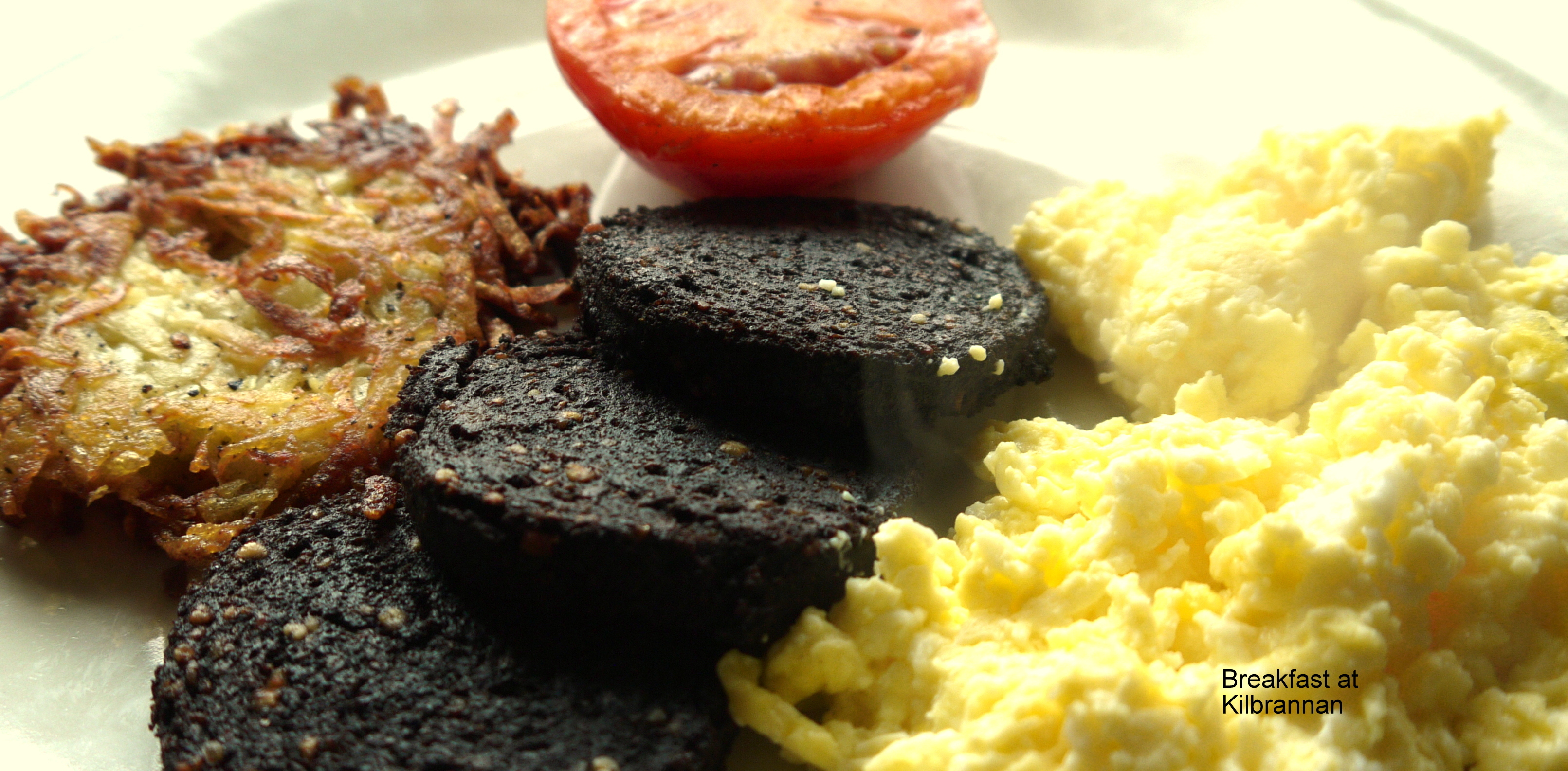 photo of scrambled egg, hash brown, fresh tomato and black pudding